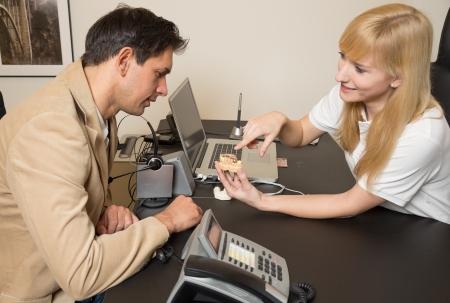 onlays: Técnico dental que muestra un modelo de una prótesis dental a un cliente o paciente en su oficina Foto de archivo