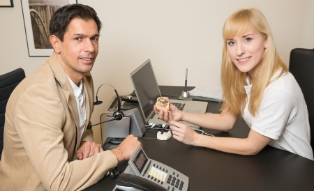 onlays: T�cnico dental que muestra un modelo de una pr�tesis dental a un cliente o paciente en su oficina Foto de archivo