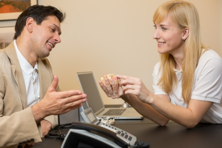 onlays: Dental technicial showing a model of a dental prosthesis to a customer or patient in her office Stock Photo