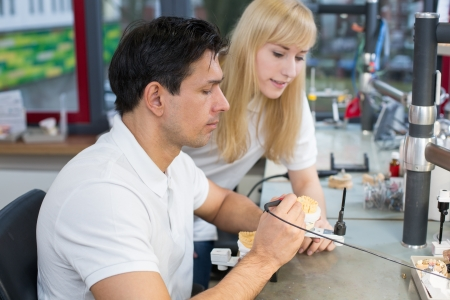 Instructor in a dental lab instructing an apprentice photo