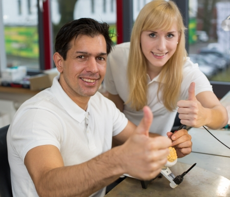 onlays: Dos técnicos dentales que muestran los pulgares en el trabajo en un laboratorio