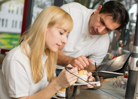instructing: Dental technician instructing an apprentice in producing a dental prosthesis