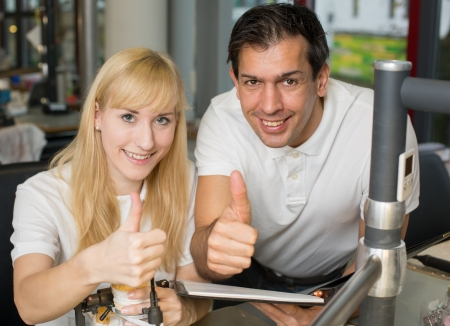 onlays: Two dental technicians showing thumbs up in a lab Stock Photo