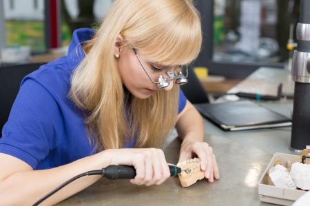 onlays: Técnico dental con lupas quirúrgicas pulido de diente de oro en un laboratorio