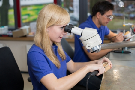 onlays: Dental technician producing a prosthesis under a microscope Stock Photo