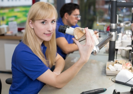 inlays: Dental technician producing a prosthesis under a microscope Stock Photo