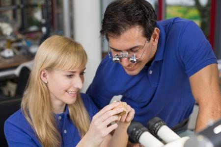 onlays: Técnico dental o aprendiz que muestra una prótesis a un colega o instructor
