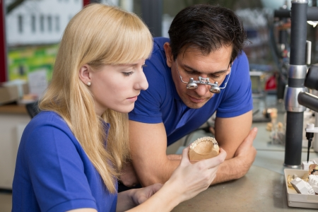 onlays: Dental technician or apprentice showing a prosthesis to a collegue or instructor Stock Photo