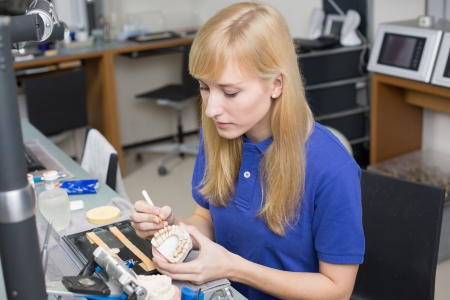 Dental lab technician applying porcelain to dentition mold in a lab
