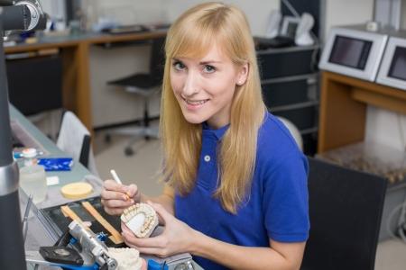 dentition: Tecnico di laboratorio dentale porcellana applicando alla muffa dentizione in un laboratorio