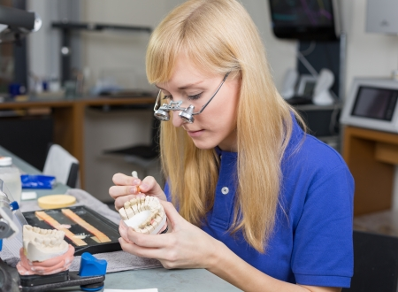 Dental lab technician with surgical loupes applying porcelain to dentition mold in a lab photo