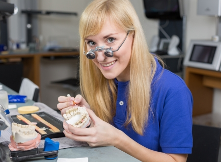 inlays: Dental lab technician with surgical loupes applying porcelain to dentition mold in a lab Stock Photo