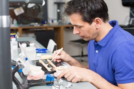 prosthodontics: Tecnico di laboratorio dentale con occhialini chirurgici appying porcellana alla muffa dentizione