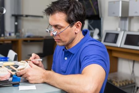 onlays: Técnico de laboratorio dental con lupas quirúrgicas appying porcelana para moldear dentición Foto de archivo