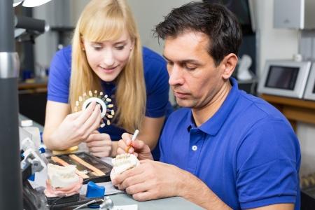 onlays: Dos técnicos dentales con muestras de color de elegir el color adecuado para porcelana dental
