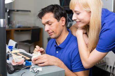 onlays: Mujer mirando porcelana t�cnico dental aplicaci�n de moldear con un cepillo