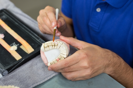 dentition: Closeup of a dental technician applying porcelain to a dentition mold with a brush in a lab