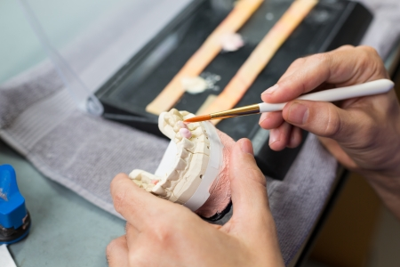 prosthetics: Closeup of a dental technician applying porcelain to a dentition mold with a brush in a lab