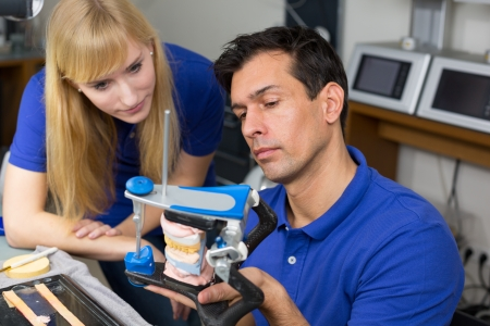 inlays: Two dental technicians looking at articulator in a dental lab