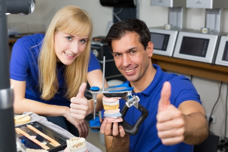 inlays: Two dental technicians with articulator in a dental lab showing thumbs up Stock Photo