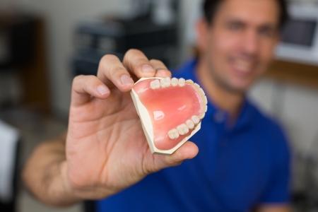 onlays: Técnico dental que presenta prótesis dental en un laboratorio dental