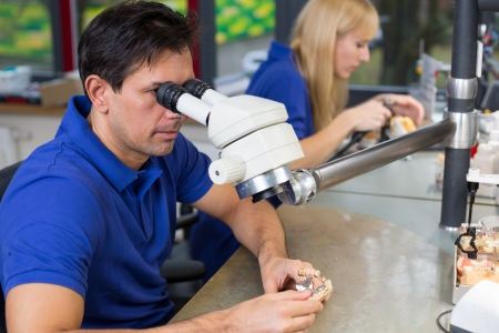 Dental technicians with microscope at work in a lab Stock Photo