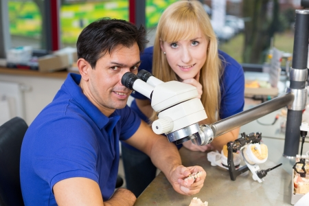 Dental technicians producing dental prosthesis under the microscope