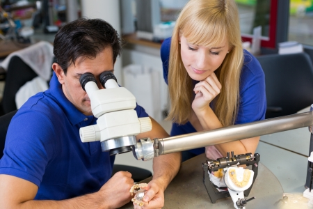 onlays: Dental technicians producing dental prosthesis under the microscope