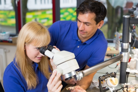 apprentice and dental technician look at prosthesis under a microscope in a lab Stock Photo - 17417178