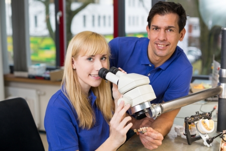 apprentice and dental technician look at prosthesis under a microscope in a lab Stock Photo - 17417200