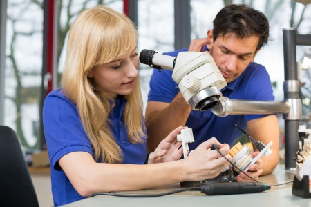 Dental technicians working on mold under a microscope in a lab Stock Photo