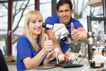 laboratorio dental: Los técnicos dentales que trabaja en un microscopio que muestra los pulgares para arriba