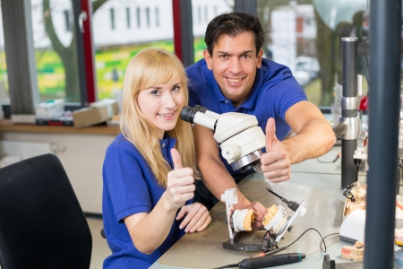 Dental technicians working at a microscope showing thumbs up Stock Photo - 17417168