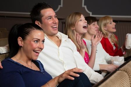 riendo: Riendo personas en un cine o en el teatro viendo una pel�cula o una obra de teatro Foto de archivo