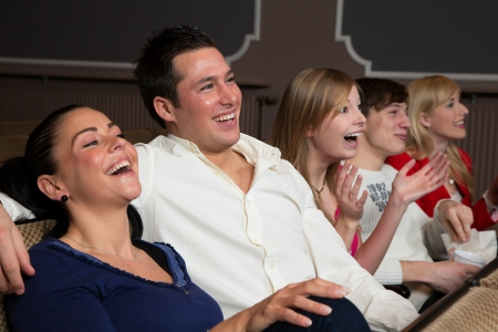 theater audience: Laughing people in a cinema or theatre watching a movie or a play