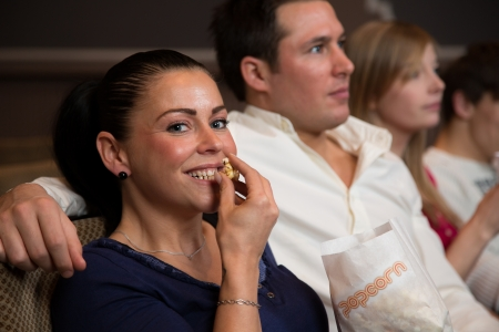 A woman enjoys an evening with friends in a cinema or theatre with popcorn photo
