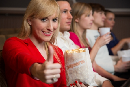 woman in cinema with a bag of popcorn showing thumbs up photo