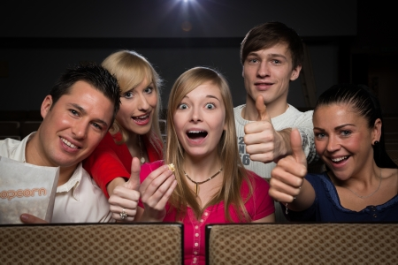 Group of happy people having fun in a cinema or movie theatre photo