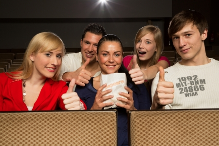 People in a movie theatre having fun and showing thumbs up photo