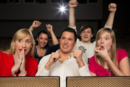 Audience in movie theatre cheering and applauding photo