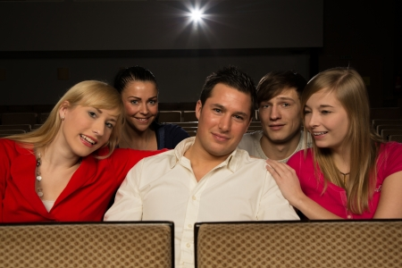 Group of people enjoying themselves in a cinema or movie theatre photo