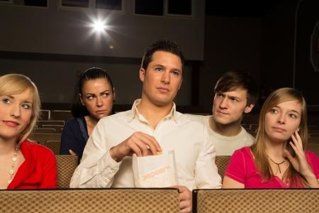 molesto: Hombre alto en una sala de cine o el cine bloqueando la vista de la gente detrás de él