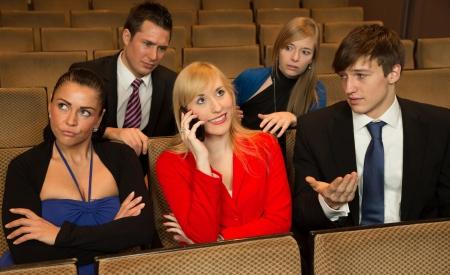molesto: Mujer en el público haciendo otros miembros del público enojado con un teléfono celular Foto de archivo