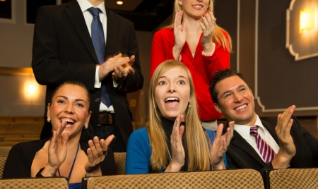Audience in a theatre, on a concert or in a cinema clapping and applauding photo