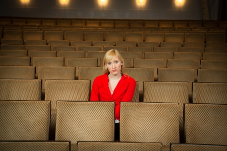 lonesome: Single woman sitting lonely in an empty cinema or theatre