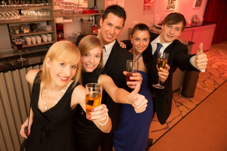 Group of five people drinking and celebrating in a bar photo