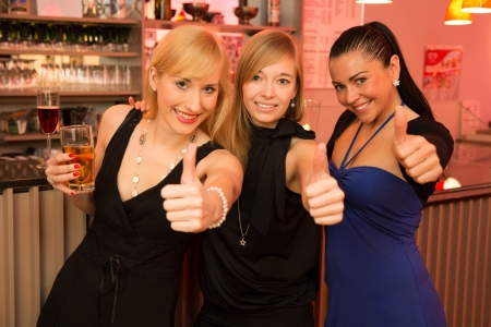 Tres hermosas mujeres bebiendo y festejando en un bar, ya que muestran los pulgares para arriba en la c?mara Foto de archivo - 17797988