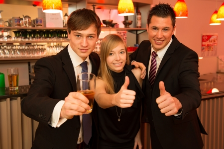 Three friends in a bar showing thumbs up Stock Photo - 17797973