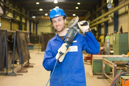 Construction worker with helmet and angle grinder posing in assembly hall photo