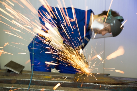 A construction worker using an angle grinder producing a lot of sparks photo